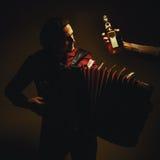 Joueur d'accordéon et bouteille chromatiques de boisson alcoolisée photographie stock