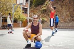 Joueur de basket avec le basket-ball se reposant au terrain de basket Image libre de droits