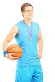 Joueur de basket de sourire posant avec la médaille d'or et basketbal Photographie stock