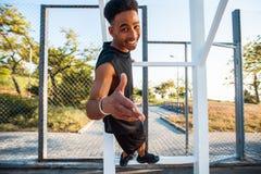 Joueur de basket heureux regardant à l'appareil-photo sur un terrain de basket photographie stock