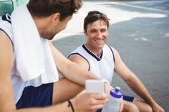 Joueur de basket montrant le téléphone portable à l'ami Image stock