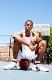 Joueur de basket s'asseyant sur la bille photographie stock libre de droits
