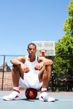 Joueur de basket s'asseyant sur la bille photographie stock