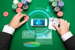 Joueur de casino avec les cartes, le smartphone et les puces Photographie stock libre de droits