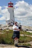Joueur de cornemuse à la crique de Peggy, la Nouvelle-Écosse Image stock