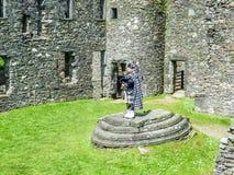 Joueur de cornemuse écossais traditionnel aux ruines du château de Kilchurn Images stock