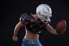 Joueur de football américain avec le casque de port de boule et les boucliers protecteurs Photographie stock libre de droits