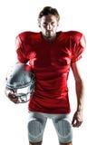 Joueur de football américain dans le débardeur rouge tenant le casque photographie stock