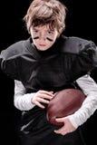 Joueur de football américain de petit garçon tenant la boule de rugby et regardant l'appareil-photo photos stock