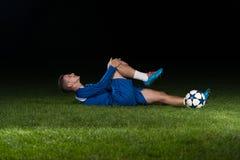Joueur de football blessé se trouvant au sol images libres de droits