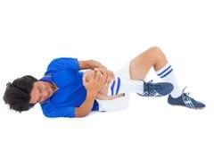 Joueur de football dans le mensonge bleu blessé Photo stock