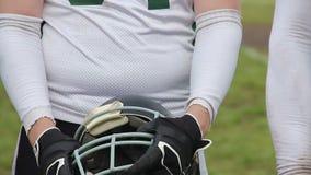 Joueur de football discipliné tenant le casque dans des mains, équipe se préparant au match clips vidéos