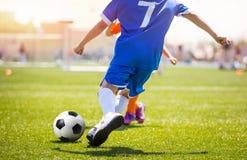 Joueur de football donnant un coup de pied la boule sur le lancement d'herbe But de marquage de butée du football Images stock