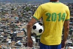 Joueur 2014 de football du Brésil avec le taudis Rio de Favela de ballon de football Photographie stock