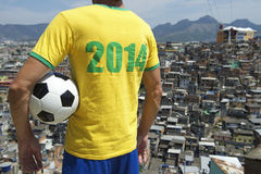Joueur 2014 de football du Brésil avec le taudis Rio de Favela de ballon de football Photo stock