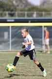 Joueur de football du football de la jeunesse de filles donnant un coup de pied la boule Images libres de droits