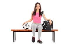 Joueur de football féminin s'asseyant sur un banc Photo stock
