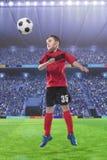 Joueur de football frappant la boule avec la tête sur un stade de football Images stock