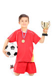 Joueur de football junior tenant une boule et une tasse d'or Photos stock