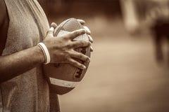 Joueur de football am?ricain retenant la bille photographie stock