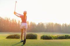 Joueur de golf asiatique de femme faisant la pièce en t d'oscillation de golf le temps vert de soirée de coucher du soleil, elle  Photos stock