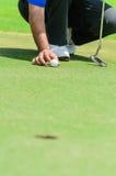 Joueur de golf asiatique s'accroupissant pour déposer Images libres de droits