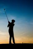 Joueur de golf féminin aîné au coucher du soleil Image libre de droits