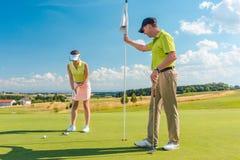 Joueur de golf féminin prêt à frapper la boule sous l'instruction de son professeur Image libre de droits