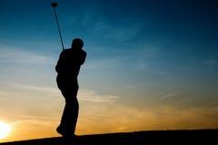 Joueur de golf mâle aîné au coucher du soleil Images libres de droits