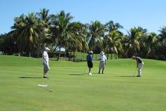 Joueur de golf masculin faisant son putt avec la partie à quatre image stock