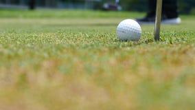 Joueur de golf mettant la boule dans le trou, seulement les pieds et le fer à voir Image stock