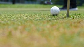 Joueur de golf mettant la boule dans le trou, seulement les pieds et le fer à voir Photographie stock libre de droits
