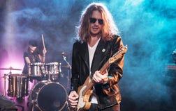 Joueur de guitare électrique avec la bande de rock exécutant la musique de hard rock images stock