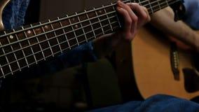Joueur de guitare basse de musicien L'homme lance les ficelles avec sa main droite, et avec sa gauche il maintient les cordes mus banque de vidéos