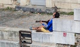 Joueur de guitare s'exposant au soleil sur les banques en pierre de la Seine Photo libre de droits