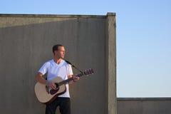 Joueur de guitare sur le toit jouant la guitare acoustique Photographie stock libre de droits