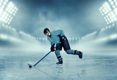 Joueur de hockey de glace dans des poses d'équipement sur le stade Image libre de droits