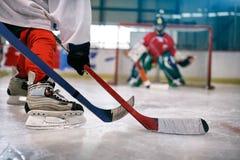 Joueur de hockey de glace dans l'action donnant un coup de pied avec le bâton photos stock
