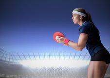 Joueur de ping-pong contre le stade avec les lumières lumineuses et le ciel bleu-foncé Photo stock