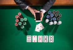 Joueur de poker avec le smartphone Photographie stock libre de droits