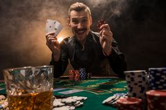 Joueur de poker beau avec deux as dans ses mains et puces se reposant à la table de tisonnier dans une chambre noire complètement image libre de droits
