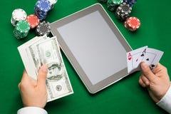 Joueur de poker de casino avec les cartes, le comprimé et les puces Image stock