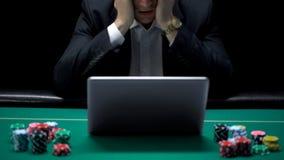 Joueur de poker devant l'ordinateur portable, jeu sur Internet perdant, dépendance de jeu faillite photos stock
