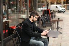 Joueur de poker en ligne à l'aide du comprimé à la table de café dedans Images stock