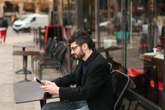 Joueur de poker en ligne à l'aide du comprimé à la table de café dedans Photographie stock