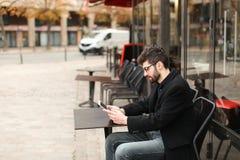 Joueur de poker en ligne à l'aide du comprimé à la table de café dedans Images libres de droits