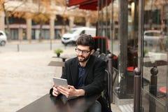 Joueur de poker en ligne à l'aide du comprimé à la table de café dedans Image libre de droits