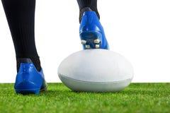 Joueur de rugby posant des pieds sur la boule Photos libres de droits