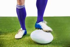 Joueur de rugby posant des pieds sur la boule Images stock