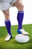 Joueur de rugby posant des pieds sur la boule Photographie stock libre de droits